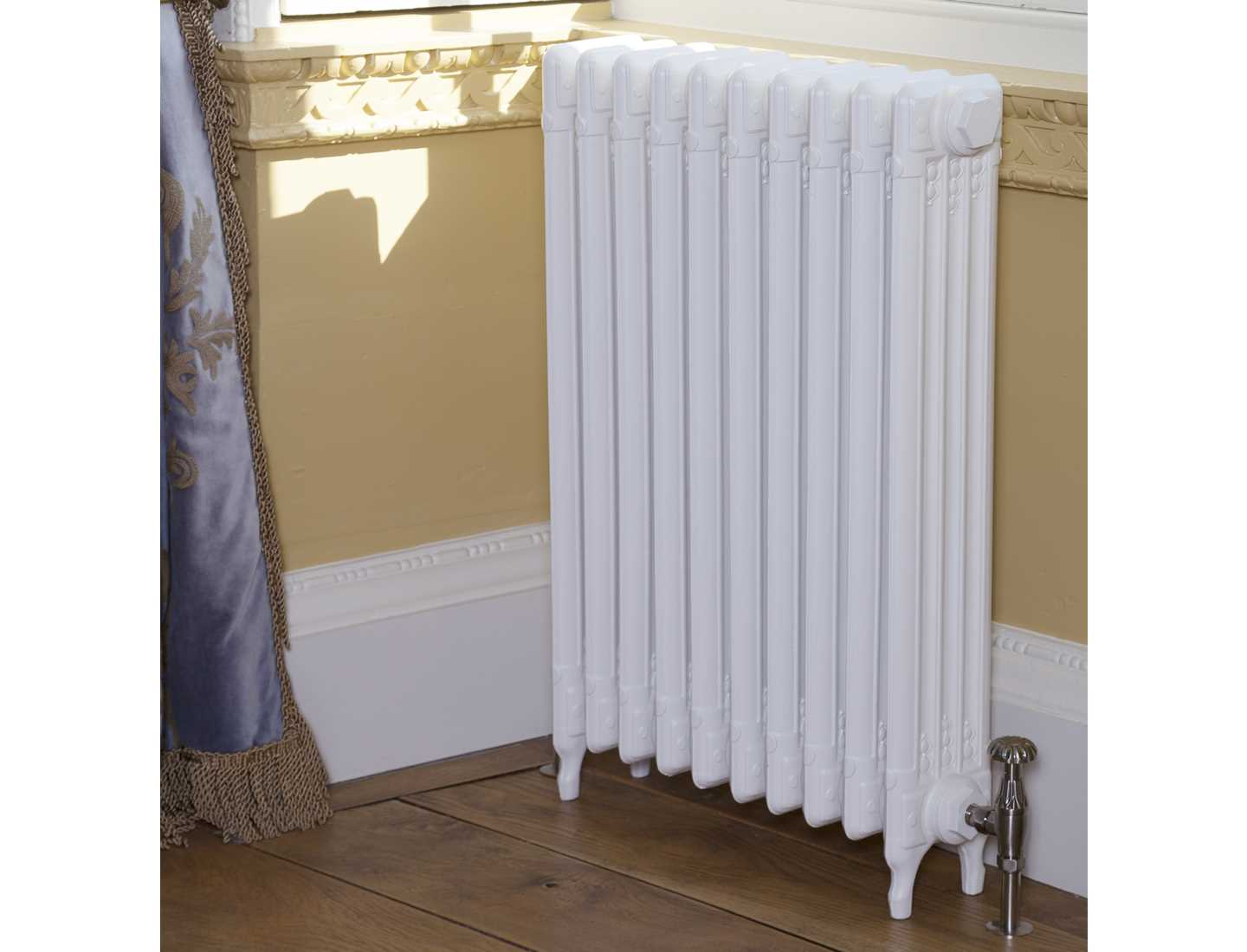 L'Art Deco cast radiator painted in parchment white with chrome valve